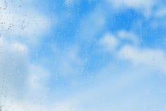 Le fond bleu texturisé du ciel, l'eau naturelle chute sur le verre de fenêtre, texture de pluie Concept de clair, pur, lumineux Photos libres de droits
