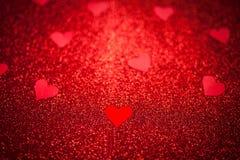 Le fond brillant rouge avec de petits coeurs rouges, amour, jour du ` s de Valentine, donnent au fond une consistance rugueuse ab Photos stock