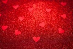 Le fond brillant rouge avec de petits coeurs rouges, amour, jour du ` s de Valentine, donnent au fond une consistance rugueuse ab Photo libre de droits