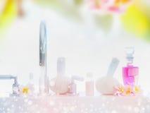 Le fond clair de station thermale ou de bien-être avec la baignoire, les produits de soin de corps, les timbres de massage et le  Photos stock
