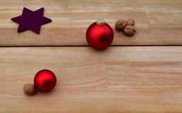 Le fond de Christmassy avec des noix et les ornements rouges de boule wodden dessus des planches Photographie stock libre de droits