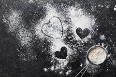 Le fond de cuisson avec de la farine et le coeur forment sur la table de noir de cuisine de ci-dessus pour la cuisson de jour de  Photographie stock