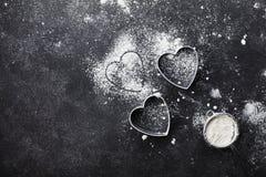 Le fond de cuisson avec de la farine et le coeur forment sur la vue supérieure de table de noir de cuisine pour la cuisson de jou Photo libre de droits