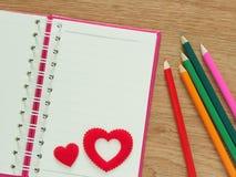 Le fond de jour de valentines avec les coeurs rouges, le livre pour le journal intime et la couleur crayonnent sur le plancher en Photo stock