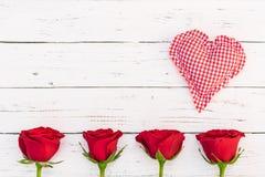 Le fond de jour de mères avec le coeur et les roses rouges de tissu fleurit sur le bois de vintage Photographie stock libre de droits