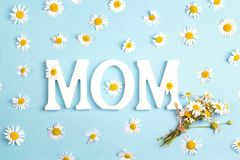 Le fond de jour de mères avec les lettres et la camomille fleurit sur bleu Photographie stock