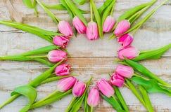 Le fond de jour de valentines avec la forme de coeur des tulipes roses fleurit sur le bois de vintage avec l'espace pour le texte Photos stock