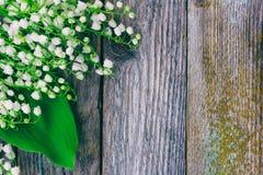 Le fond de la vieille grange en bois embarque avec les fleurs de forêt, lis de la vallée photographie stock libre de droits