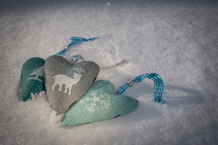 Le fond de neige avec trois coeurs avec un hiver élégant imprime Photographie stock libre de droits