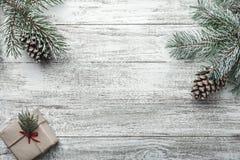 Le fond de Noël avec le boîte-cadeau et le sapin s'embranche sur la vieille table en bois Fond de vacances Image libre de droits
