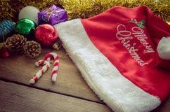 Le fond de Noël et les chapeaux Santa sur le bois - modifiez la tonalité le vintage photographie stock libre de droits