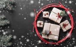 Le fond de Noël pendant des vacances d'hiver avec les cadeaux de Noël et le sapin s'embranche symbole vert de neige avec l'effet  Photos libres de droits