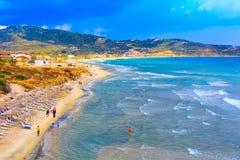 Le fond de plage avec l'eau de mer de turquoise ondule et des parapluies, Grèce Photo stock