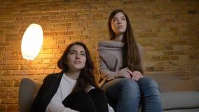 Le fond de plan rapproché vers le haut du portrait de deux jeunes jolies femmes observant un film TV dans un appartement conforta photos stock