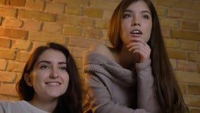 Le fond de plan rapproché vers le haut du portrait de deux jeunes jolies femmes regardant la TV avec l'excitation dans un apparte image libre de droits