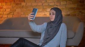 Le fond de plan rapproché vers le haut de la pousse du jeune adolescent féminin musulman attirant prenant des selfies au téléphon clips vidéos
