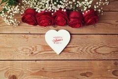 Le fond de Saint-Valentin avec les roses rouges et le coeur forment sur la table en bois Vue de ci-avant Photos libres de droits