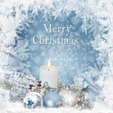 Le fond de salutation de Noël avec des bougies, pin s'embranche, des boules sur un fond bleu avec un modèle givré Photographie stock libre de droits