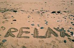 Le fond de vacances avec DÉTENDENT le mot écrit sur la plage sablonneuse Fond de vacances Été Dans détendez l'humeur Photo libre de droits