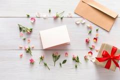 Le fond de Valentine avec la carte de voeux de papier vide et la boîte actuelle dans la rose de rose fleurit le cadre Photos stock