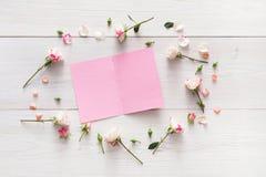 Le fond de Valentine avec la carte de voeux de papier vide avec l'espace de copie dans la rose de rose fleurit le cadre sur le bo Photo stock