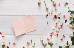 Le fond de Valentine avec la rose dispersée de rose fleurit et des pétales sur le bois rustique blanc Images stock