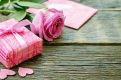 Le fond de Valentine avec un cadeau, une fleur et une carte Photos stock