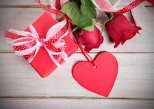 Le fond de Valentine du boîte-cadeau, les roses rouges et le cadeau rouge étiquettent Images stock