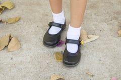 Le fond a donné au ciment une consistance rugueuse extérieur sur les planchers avec la marche de fille de chaussures photo libre de droits