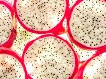 Le fond du dos a allumé les tranches mûres fraîches de fruit du dragon de pitaya Photos stock