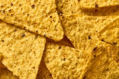 Le fond du plan rapproché triangulaire jaune de nachos de maïs photographie stock