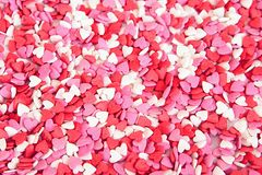 Le fond du sucre coloré arrose aux coeurs Images stock