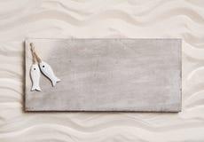 Le fond en bois avec le sable et deux poissons sur un signe aiment des mes Photo stock