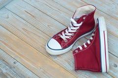 Le fond en bois grunge avec rouge et le blanc a utilisé des espadrilles de toile de vintage Photos stock