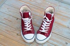 Le fond en bois grunge avec rouge et le blanc a utilisé des espadrilles de toile de vintage Images stock