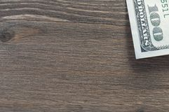 Le fond est un arbre texturisé foncé, dans le bord du bord cent billets d'un dollar images stock