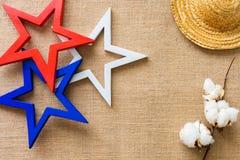Le fond plat de configuration avec les étoiles en bois, le chapeau de paille et le coton fleurissent sur le tissu de toile de jut Images libres de droits