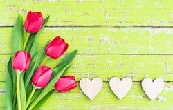 Le fond romantique d'amour avec des coeurs frontière et groupe des tulipes rouges fleurit sur le bois vert avec l'espace de copie Photo stock