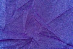 Le fond, texture de tissu a drapé le lycra pourpre Photographie stock libre de droits
