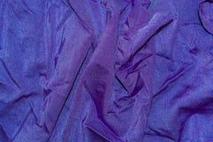Le fond, texture de tissu a drapé le lycra pourpre Photographie stock
