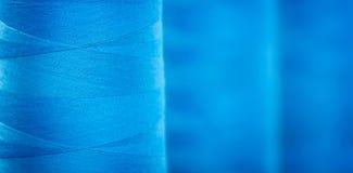 Le fond texturisé bleu de bannière de Web, les bobines en gros plan avec le bleu coloré filètent pour les machines textiles indus Photos libres de droits