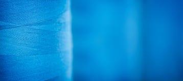 Le fond texturisé bleu de bannière de Web, les bobines en gros plan avec le bleu coloré filètent pour les machines textiles indus Images libres de droits