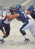 Le football 2011 de NCAA - bloquant dans la neige Photos stock