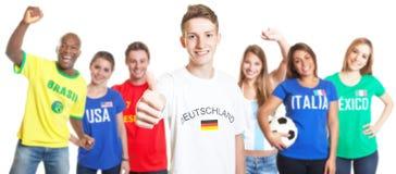 Le football allemand avec les cheveux blonds montrant le pouce avec d'autres fans Photographie stock