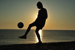 Le football au coucher du soleil Photographie stock