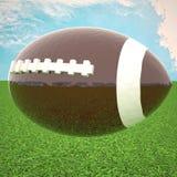 Le football au-dessus de l'herbe verte, sous le ciel bleu Photographie stock