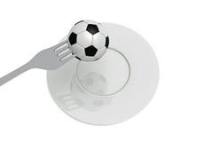 Le football comme nourriture : le football, fourchette et plat Photos stock