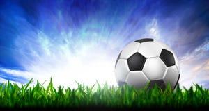 Le football dans l'herbe verte au-dessus d'un ciel crépusculaire Image stock