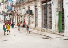 Le football de jeu de quatre garçons dans la rue urbaine comme personnes marchent par surrou Photos stock