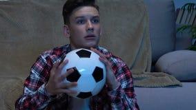 Le football de observation d'adolescent à la maison, avec émotion encourageant pour le favori coulent banque de vidéos